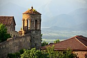 Medieval stone tower of the fortress of Telavi with green landscape and Caucasus mountains in the background, Kakheti, Eastern Georgia