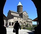 Monk with briefcase arrives in the courtyard of the monastery Alaverdi, Kakheti, East Georgia