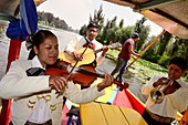 Mexican marijuana musicians and the boatman on colorful boats on the canals of Xochimilco, Mexico City, Mexico