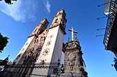 View from below of the towers of the Igleisia de Santa Prisca in the colonial old town of Taxco, Mexico