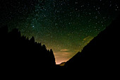 Mountain and forest silhouettes in front of the starry sky. Obersee. Switzerland