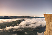 Man stands in sunrise on the edge of Preikestolen. Below him clouds and the Lysefjord. Norway
