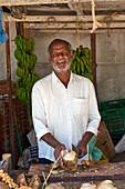 Fruchtverkäufer mit Kokosnuss an seinem Stand in Salala, Oman