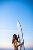 Side view shot of woman in yellow bikini standing with surfboard