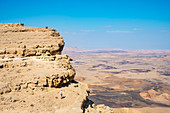 Distant view shot of hiker standing near edge of Makhtesh Ramon Crater, Negev Desert, Mitzpe Ramon, Southern District, Israel