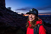 Portrait of female hiker wearing headlamp standing at Cathedral Rock and smiling at camera, Arizona, USA
