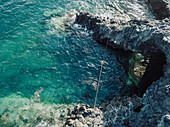 Aerial view of young shirtless man balancing across tightrope over coastal water,†Tenerife, Canary Islands, Spain