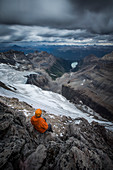View from above of hiker in safety helmet sitting in mountains, Lake O'Hara, Yoho National Park, Alberta, Canada