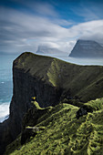 Majestic natural scenery with view of cliffs and person standing with arms raised, Kalsoy, Faroe Islands