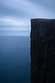 Majestic view with person standing on edge of steep vertical cliff on seashore, Faroe Islands