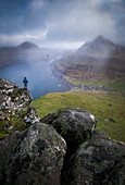 Person standing on rock formation and looking at view of landscape with mountains and seashore, Funningur, Faroe Islands