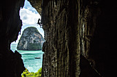 Side view silhouette of man rock climbing in beautiful natural scenery on edge of cave, Phra Nang Beach, Krabi, Thailand