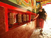 A hiker is turning Buddhist prayer wheels to spread the mantras, asking for good luck. The trek to Everest Base Camp (EBC) is possibly the most dramatic and picturesque in the Nepalese Himalaya. Not only will you stand face to face with Mount Everest, Sagarmatha in Nepali language, at 8,848 m (29,029 ft), but you will be following in the footsteps of great mountaineers like Edmund Hillary and Tenzing Norgay. The trek is scenic and offers ever-changing Himalayan scenery through forests, hills and quaint villages. A great sense of anticipation builds as you trek up the Khumbu Valley, passing thr