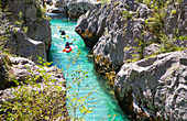 Kayakkers on the emerald Soca near Bovec in Slovenia. This green colored river, originating in the Triglav mountains, is famous for all kinds of white water activities.