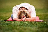 A young athletic blonde woman in her twenties enjoying yoga on a bright red mat in the grass of Jackson, Wyoming, USA
