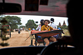 View from car interior of Asian tourist using selfie sticks to take smartphone photos from a horse cart as they ride towards a Buddhist temple at Bagan, Mandalay Region, Myanmar. The site is one of the most famous tourists destinations in the Southeast Asian country.