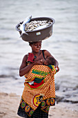 Mother breastfeeding baby while carrying bowl of fish on top of head, Inhambane, Mozambique