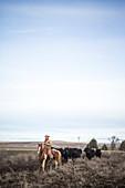 Clear sky over rancher herding cattle on horseback, Oregon, USA