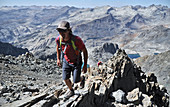 Backpackers climbing Mt Ritter on trek of Sierra High Route in Minarets Wilderness, Inyo National Forest, California, USA