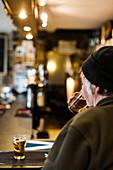 Rear view of older man enjoying glass of beer at pub, Scotland, UK