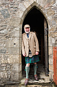 Portrait of mature man wearing traditional kilt leaning on archway of Eilean Donan Castle, Scotland, UK
