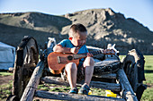 Mongol boy playing guitar while sitting on yak cart, Bunkhan, Bulgan, Mongolia