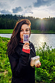 Woman holding instant camera and photograph on Colorado Trail, Colorado, USA