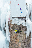 Male ice climber clinging horizontally to rocks on competition route, Ouray Ice Park, Colorado, USA