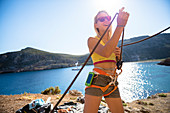 Smiling female rock climber standing wearing climbing gear, Kalymnos, Greece