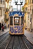 Painted tram waiting on rails across steep city street, Lisbon, Portugal