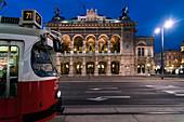 Illuminated Vienna State Opera at night with tramway in foreground, Vienna, Austria