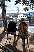 Sitting woman and woman in a hat and fur coat on a bench in Letná Park with a view of the Vltava river and the many bridges, including the Charles Bridge, Prague, the Czech Republic