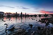 Blick auf die Karlsbrücke bei Sonnenaufgang vom Ufer der Moldau aus, Prag, Tschechien