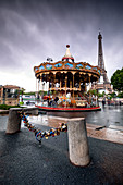 Carousel in front of the Eiffel Tower in rainy weather; in the foreground, love-locks are fastened to the chain of street-bluffing; Paris; Île-de-france; France