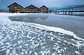 Eisblumen auf dem gefrorenen Kochelsee im Winter, Holzhütten mit Steg, Bayern, Deutschland