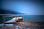 Beam of light on snow-covered wooden walkway at Walchensee in fog in winter, long exposure, Alpine foothills, Bavaria Germany