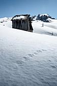 Alte Holzhütte im Schnee mit Blick auf den Passo di Giau, Dolomiten, Cortina d'Ampezzo, Belluno, Italien