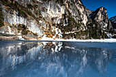 Reflection from frozen Lake Braies, in the background a walk along the mountain massif in winter, Dolomites, Lago di Braies, Braies, South Tyrol, Italy