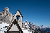 Bell tower of the chapel of San Giovanni Gualberto on the Passo di Giau in winter, in the background view of the Dolomites, Belluno, Italy