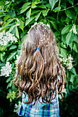 Girl with flowers in hair at blooming bush