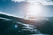 Man standing on sunny snow covered mountain, Reykjadalur, Iceland