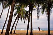 Surfer mit Surfbrett auf tropischem Strand mit Palmen, San Pancho, Nayarit, Mexiko
