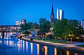 Blick über Fluss auf Kirchenturm und Büro-Hochhäuser bei Sonnenuntergang in Frankfurt, Deutschland