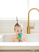 Baby girl with Mohican hairstyle holding toy while bathing in kitchen sink