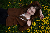 Smiling young woman lying on yellow flowers