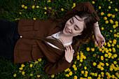 Lächelnde junge Frau liegt auf Wiese mit gelben Blumen