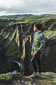 Young man standing on cliff above canyon in Kirkjub?jarklaustur, Iceland
