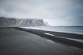 Man walking on black sand beach in Kirkjub?jarklaustur, Iceland