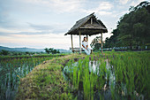 Woman sitting in hut by rice paddy in Bali, Indonesia