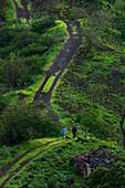 Zwei Wanderer auf einem Weg durch die grüne Landschaft im Hinterland der Insel Santiago, Kap Verde
